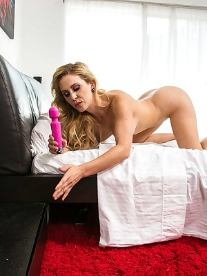 Busty blonde lady Cherie Deville toys her pussy to orgasm on her bed