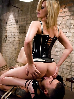 Maitresse Madeline Marlowe sits on face of humiliated man tied to the table
