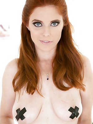 Redhead Penny Pax strips out of her sexy stockings and bares hairy bush
