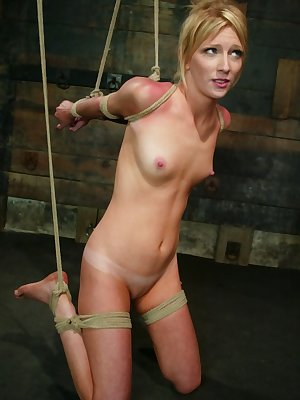 Blonde female Alexa Lynn is forced to suck cock while suspended by ropes