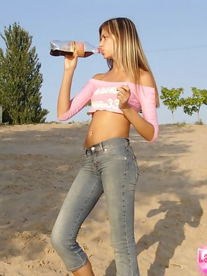 Slender young blonde amateur posing outdoors in crop top and tight jeans