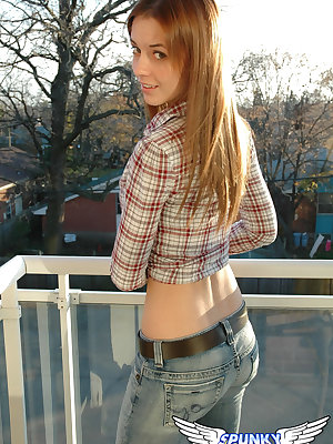 Redheaded country girl models non nude in tied up shirt and denim jeans