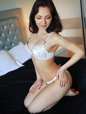 Pretty brunette Lily White peels her white panties to show freshly shaved muff