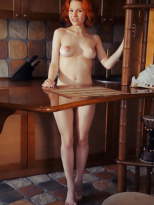 Beautiful redhead Zarina A poses naked in the kitchen pinching her nipples