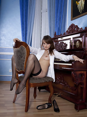 Solo model Mariara displays her trimmed muff in black stockings at the piano