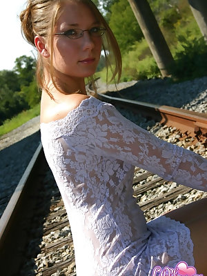 Amateur solo girl poss non nude on train tracks in tight dress and glasses