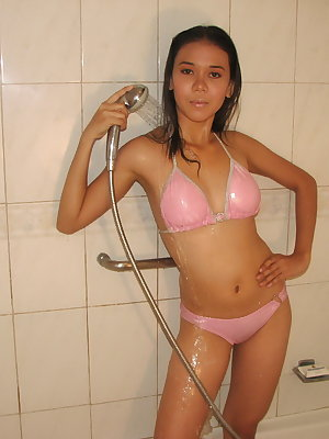 Cute young Asian girl peels her wet bikini in the shower to show her tiny tits