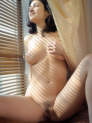 Nude brunette Zita B lets the filtered light shine on her in front of window