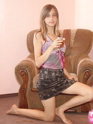Young amateur model shows bare legs in a short skirt while having a drink