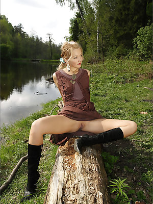 Horny slut in boots bends over on a fallen tree to show off her hot bare ass