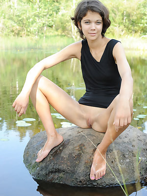 Pretty dark haired Tina removes her black dress by the pond to show tiny tits