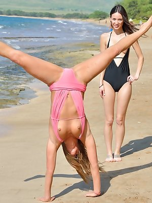 2 lesbians frolic in swimsuits at the beach before strolling in the nude