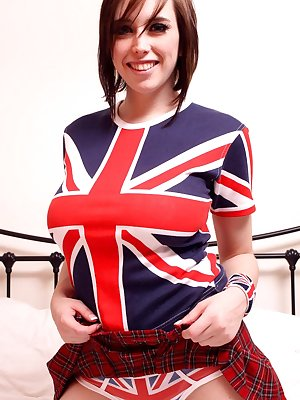 Young and busty girl strips off her Union Jack attire atop her bed