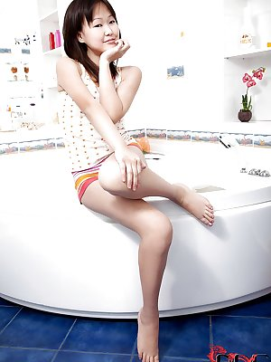 Petite asian teen having bath and teasing herself with water jets