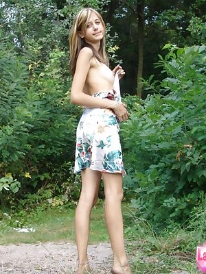 Innocent looking young girl strips naked against a backdrop of green foliage