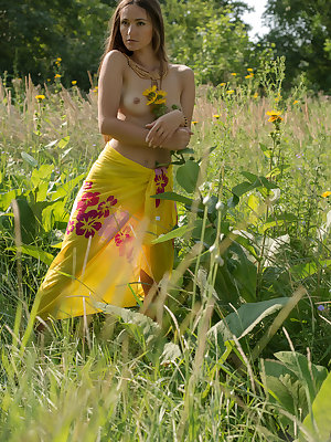 Teen solo girl with small tits takes off her wrap to pose nude among the weeds