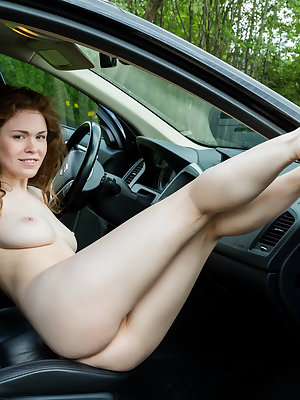 Naked naughty girl Estelle poses with long legs spread airing pussy in the car
