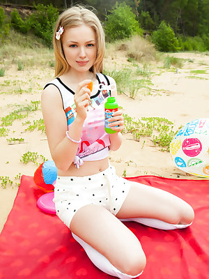 Innocent young girl blows bubbles while posing naked at the beach
