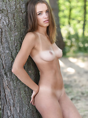 Young solo girl with a pretty face gets totally naked out in the forest