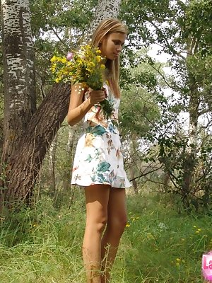 Sweet teen in short dress bending for sexy panty upskirt while picking flowers