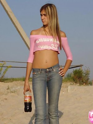 Leggy teen girl in blue jeans ducks behind a blind to flash her tits