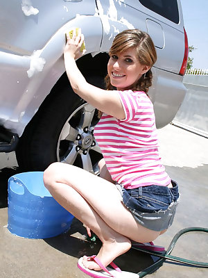 Young girl in pigtails wets her tiny tuts while washing a car in driveway