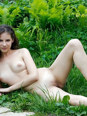 Cute outdoor girl Swan gathers flowers in the garden in the nude