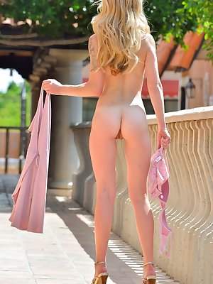 Pretty blonde Leah gets naked in the sunshine & stretches pussy lips wide open